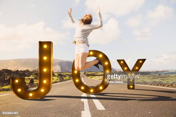Creative creation of a joy letters illuminated with light bulbs behind a happy woman jumping in middle of nice straight road during travel vacations in the Canary islands.