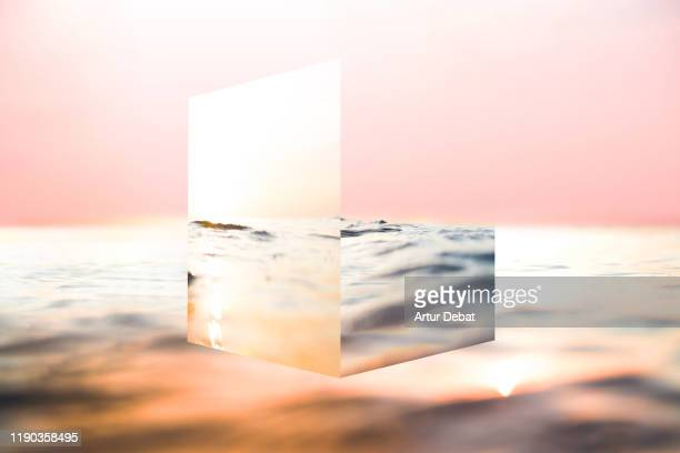 creative cube mirror playing with the sea reflections and sunset colors. - cube shape stock pictures, royalty-free photos & images