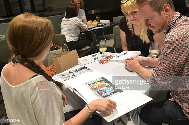 Creative directors reviewing portfolios of young creatives at Portfolio Night 10 at Lincoln Financial Field on May 23 2012 in Philadelphia...