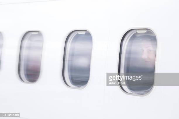 Creative double exposure composition picture of traveler woman looking through window on airplane with picture taken from outside of airplane with window reflection during landing to the destination airport.