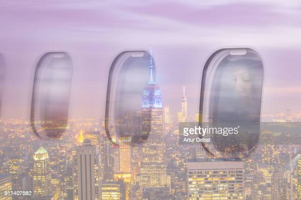 Creative double exposure composition picture of traveler woman looking through window on airplane with picture taken from outside of airplane with New York cityscape view at night reflected during landing to the destination airport.