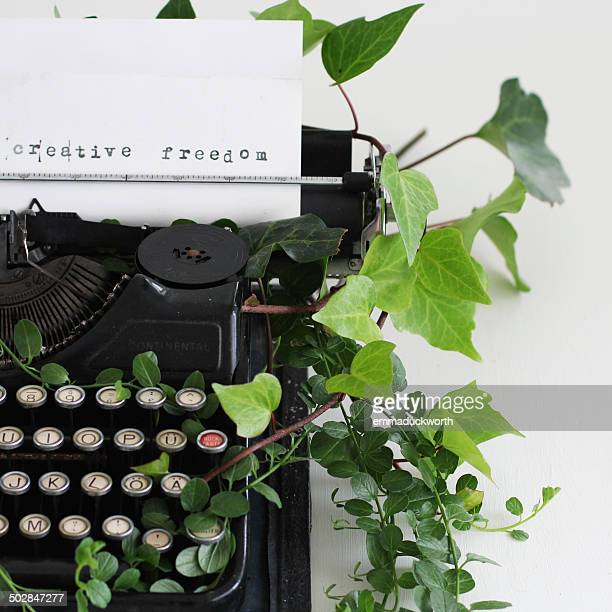 Creative Freedom typed on paper in typewriter surrounded by ivy