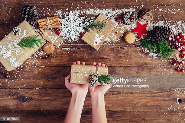 Creative hobby. Girl's hands show christmas holiday handmade present in craft paper
