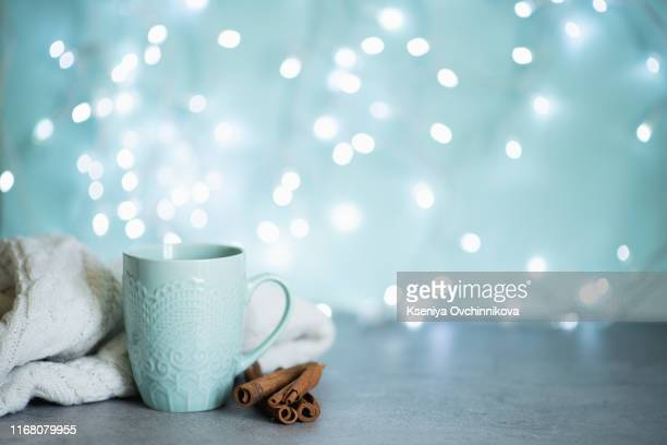 creative image of hot chocolate with cream and cinnamon stick in a blue rustic ceramic cup. the concept of winter cozy holidays. snow effect. - autumn decoration stock pictures, royalty-free photos & images