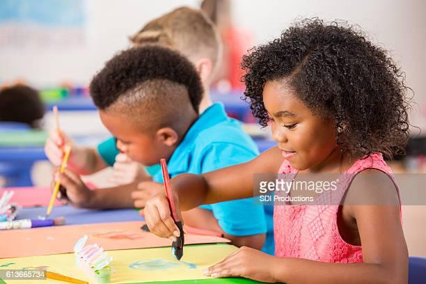 Creative kindergarten students work on painting in class