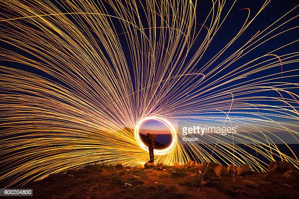 creative light painting by burning steelwool - igniting stock photos and pictures