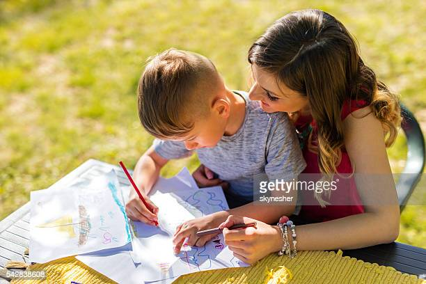 Creative little boy coloring with his mother during springtime.