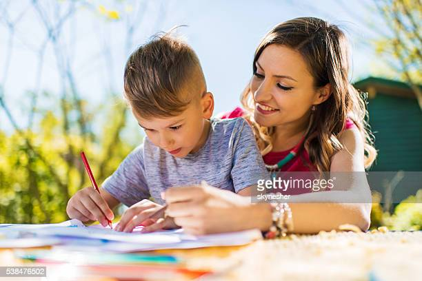 Creative little boy drawing outdoors with his smiling mother.