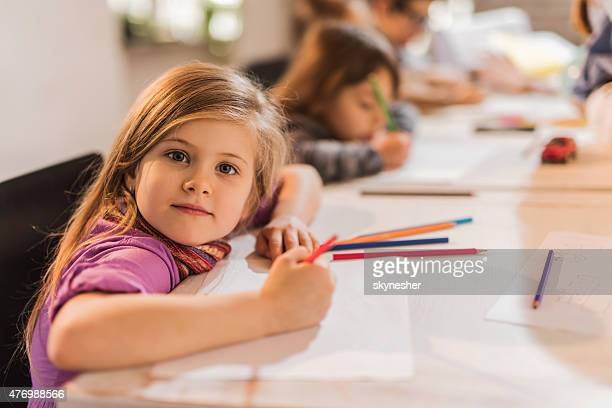 Creative little girl drawing and looking at camera.