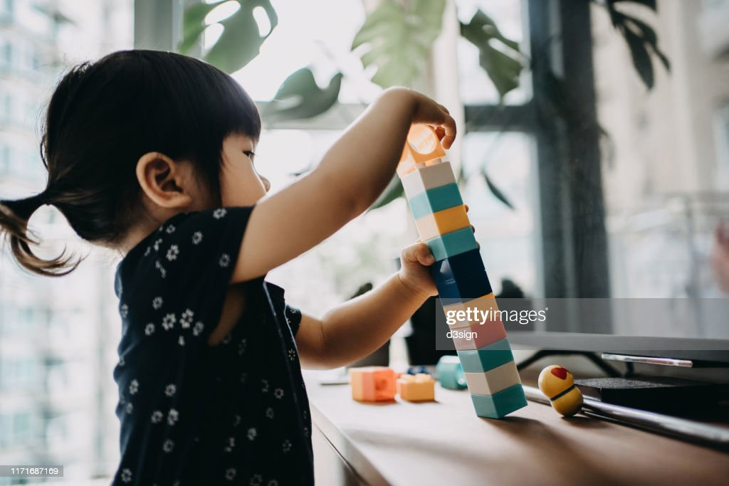 Creative little toddler girl playing with colourful building blocks at home : Stock Photo