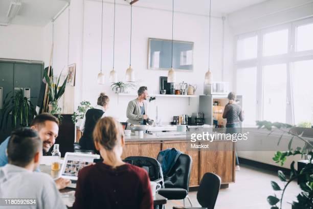 creative male and female entrepreneurs working in office - groupe moyen de personnes photos et images de collection