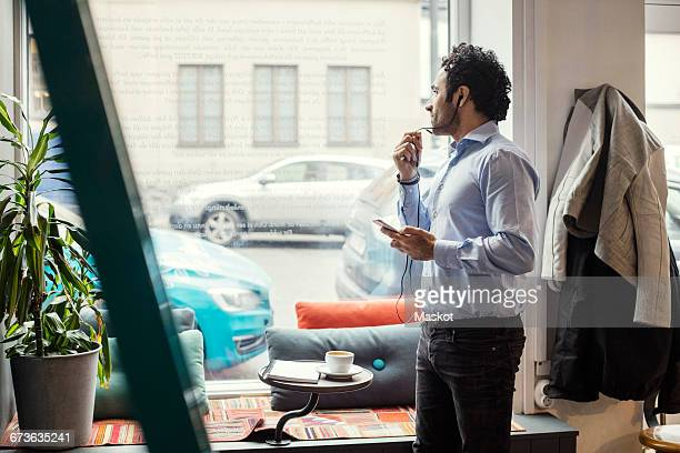 Creative man using headphones while standing against window in office