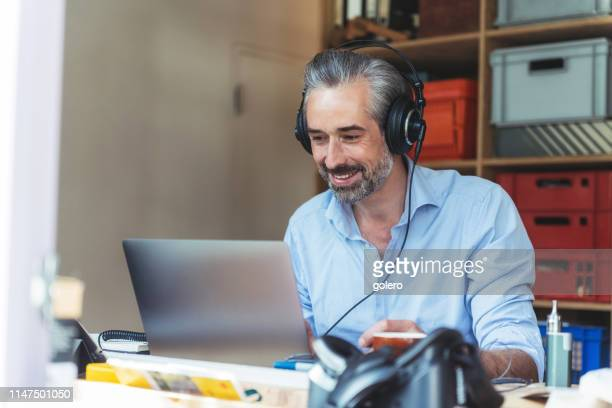 creative man with headphones working at laptop in homeoffice - live streaming stock pictures, royalty-free photos & images