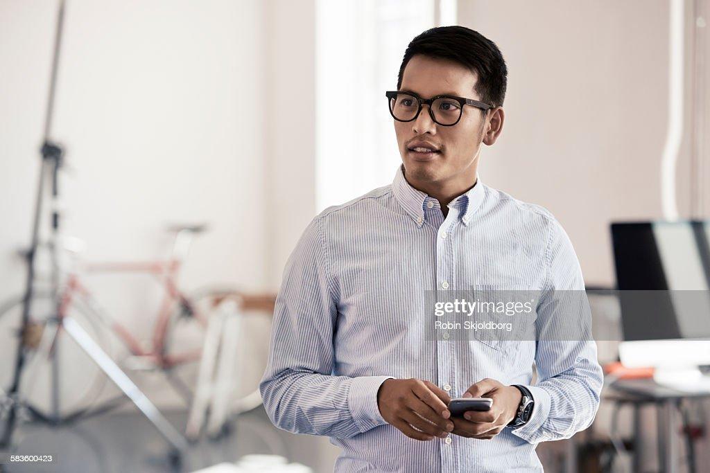 Creative Man with mobile phone in photo studio : Stock Photo