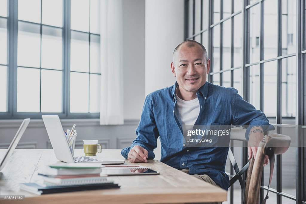 Creative mature man at desk in modern office : Stock Photo