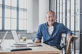 Creative mature man at desk in modern office