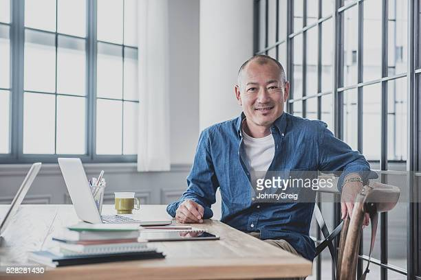 creative mature man at desk in modern office - east asian culture stock photos and pictures