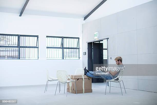 Creative office man relaxing on a chair and boxes