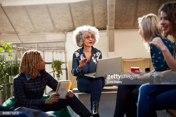 Creative people having a relaxed meeting in an industrial office space.