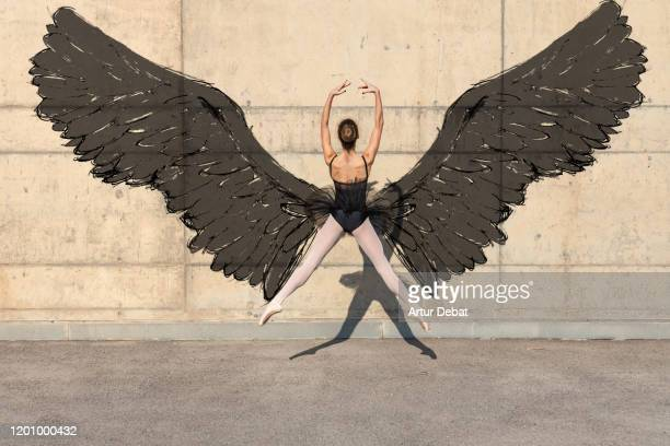 creative picture of ballerina dancing with artistic black wings painted in the wall. - gliedmaßen körperteile stock-fotos und bilder