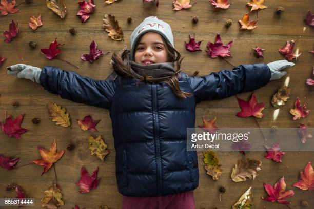 creative picture of cute girl with winter clothes in cold autumn day in a directly above picture with red autumn leaves, nice composition and wood flat lay. - winter coat stock pictures, royalty-free photos & images