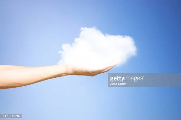 creative picture of fluffy cloud sustained by human hand. - ふわふわ ストックフォトと画像