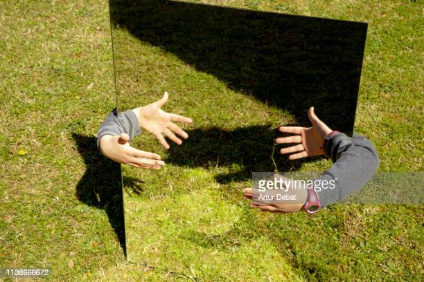 creative picture of girl playing with mirror reflection in the backyard home. - 鏡 物品 個照片及圖片檔
