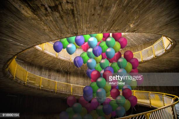 Creative picture of group of colorful helium balloons flying in the middle of cool spiral ramp in the city.