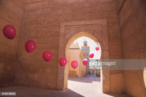 Creative picture of red helium balloons in line following each other crossing big  wall gate entry in Morocco city.