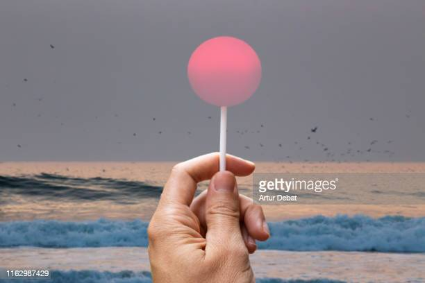 creative picture of sun like a lollipop in the beach. - vorstellungskraft stock-fotos und bilder