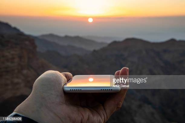 creative picture playing with the sunset reflection of the mobile phone. - jordan middle east stock pictures, royalty-free photos & images