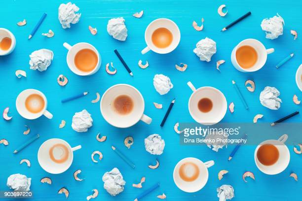 Creative profession workplace with empty coffee cups, crumpled paper balls and pencil shavings on a colorful blue background. Minimalist inspiration concept.