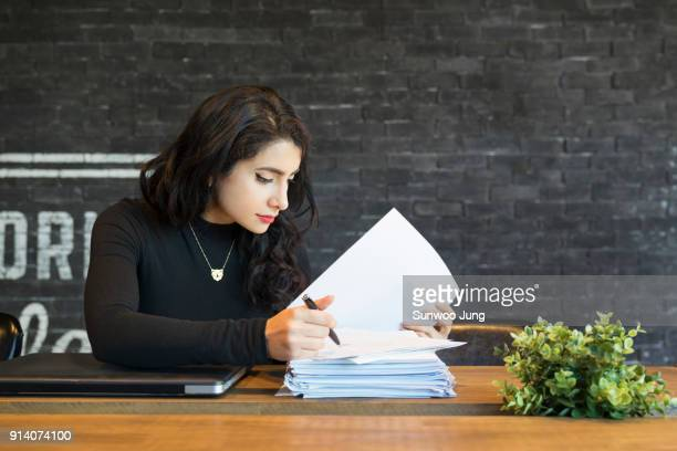 Creative professional reviewing documents in modern office