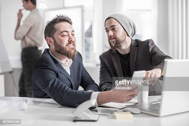 Creative professional showing cell phone to colleague at desk