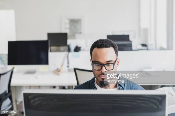 Creative professional using computer in office with glasses and facial hair