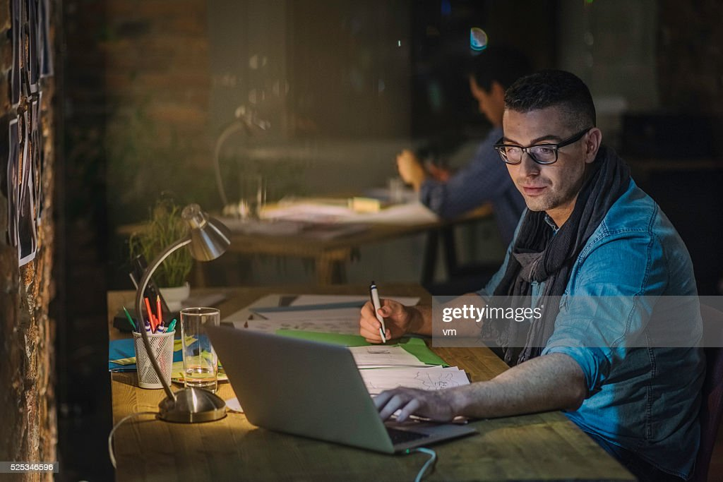 Creative professional using laptop and writing notes : Stock Photo