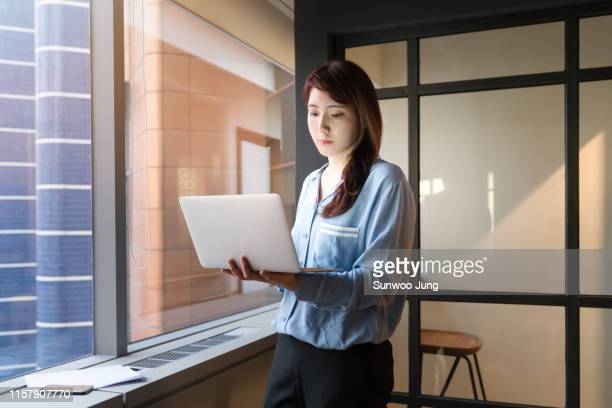 creative professional using laptop in modern office - korea stock pictures, royalty-free photos & images