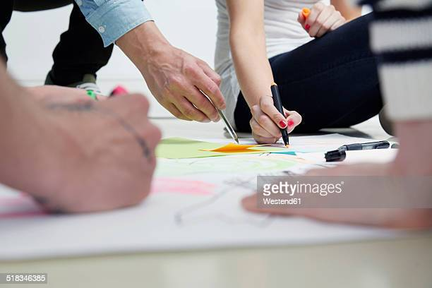 creative professionals drawing on paper - skizze stock-fotos und bilder
