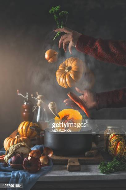 creative pumpkin soup still life with flying or falling vegetables ingredients in steaming cooking pot and woman hands - season stock pictures, royalty-free photos & images