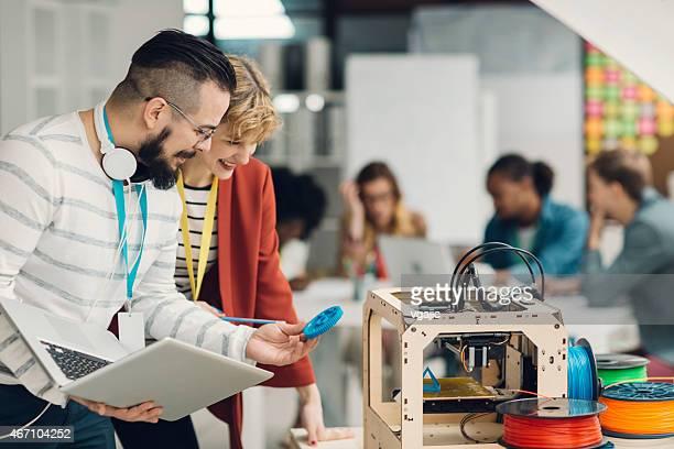 Creative équipe commerciale d'une Start-Up travaillant par imprimantes 3D.