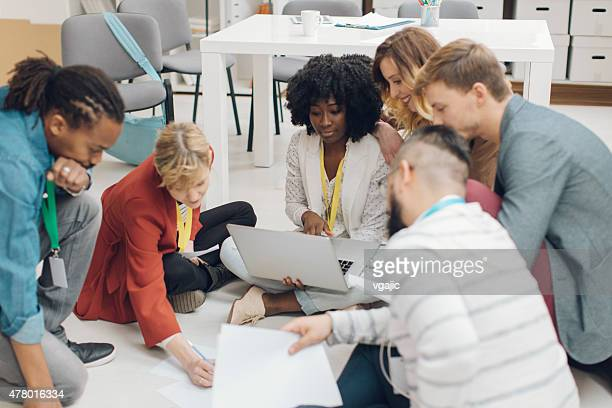Creative Startup Team Brainstorming On Floor.