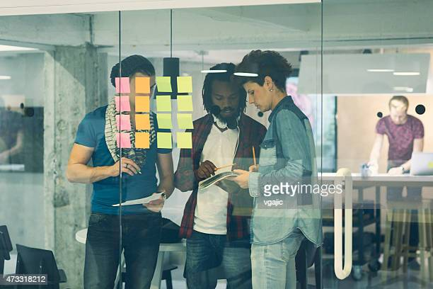 Creative Startup Team looking at sticky notes and writing.