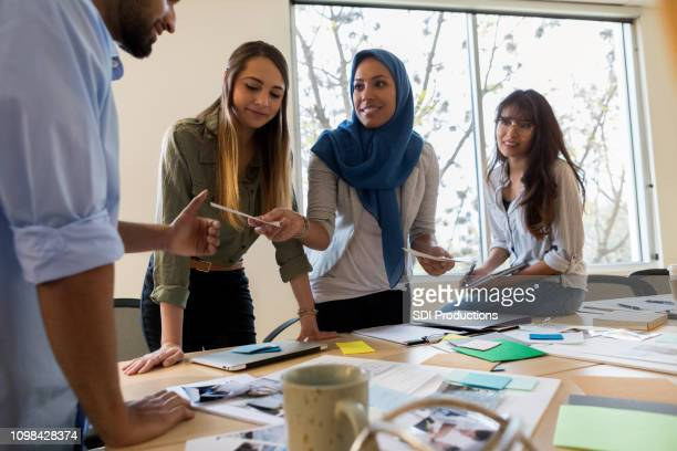 ボードルームのプロジェクトについて議論する創造的なチーム - ヒジャブ ストックフォトと画像