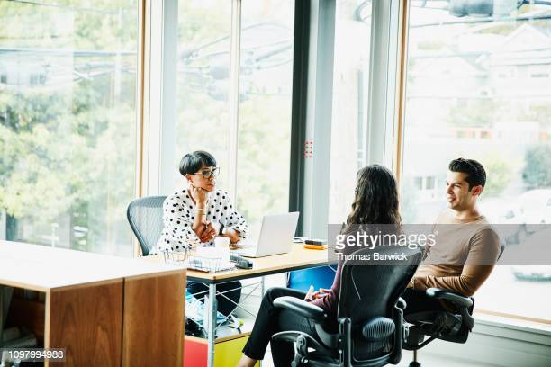 creative team in discussion while seated at workstation in design studio - agence de design photos et images de collection