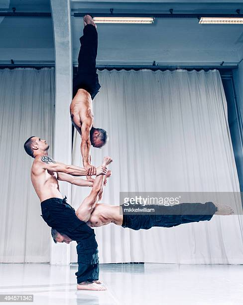 Creative teamwork with three acrobats holding balance with their strenght