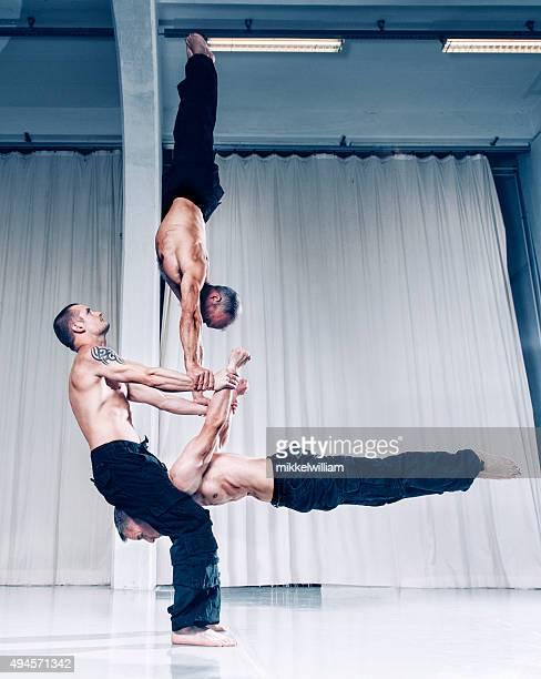 Kreative Zusammenarbeit mit drei Akrobaten halte das Gleichgewicht mit Ihrer Kraft