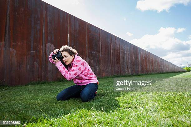 Creative woman kneeling to take pictures with digital camera