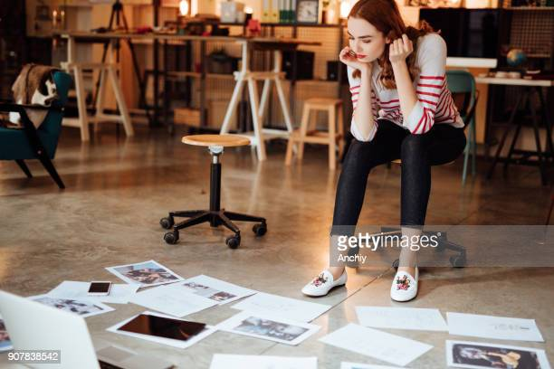 Creative woman looking at project plans laying on floor