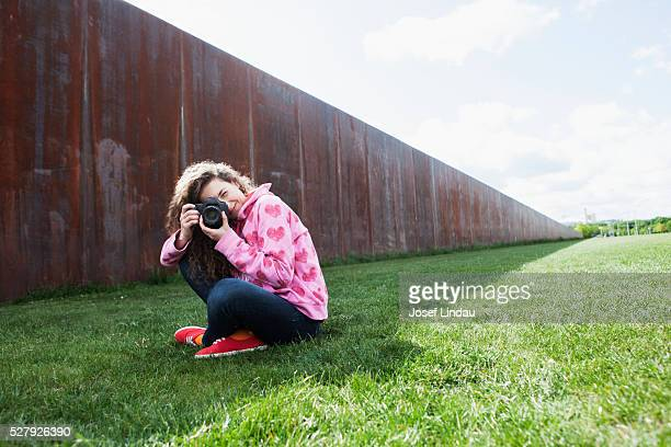 Creative woman taking pictures with digital camera