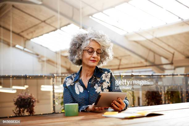 Creative woman working on a tablet in industrial office space.